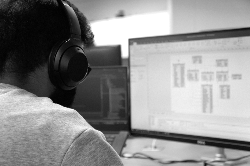 A man from Adatis with headphones on doing data science on a computer