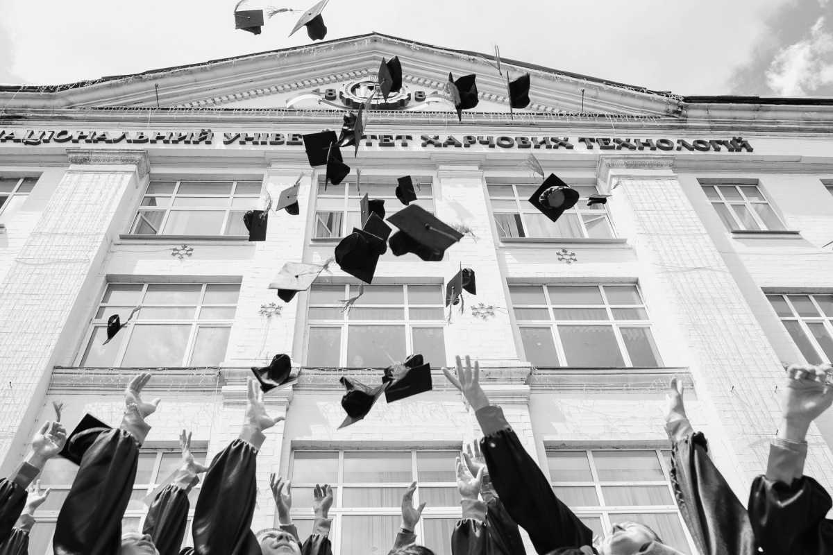 Graduation hats being thrown in the air students finishing university